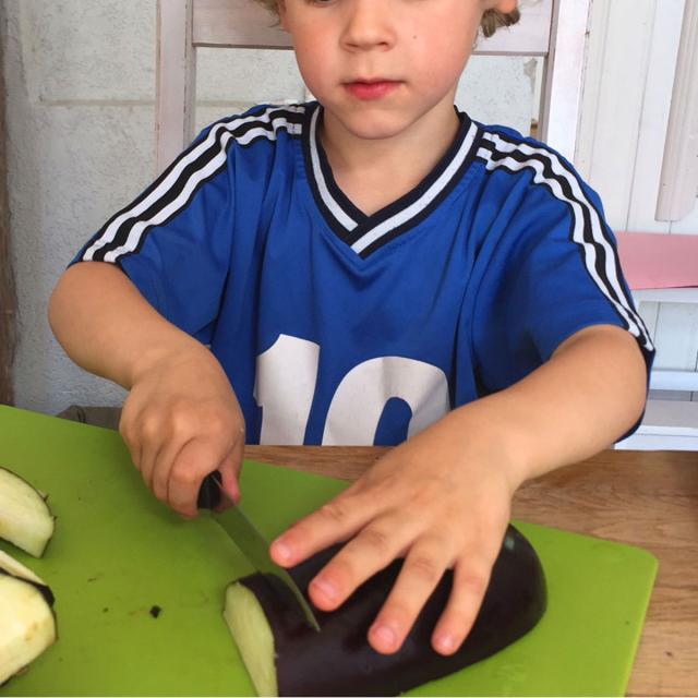 A child cuts vegetables with a knife